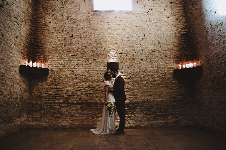 Wedding photo of a barn destination wedding and the couple in beautiful light