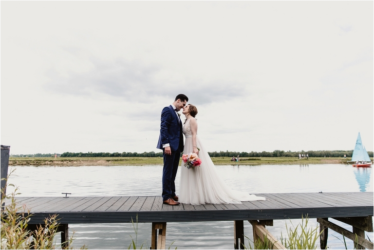 bride and groom stood by the river at the perch oxford wedding