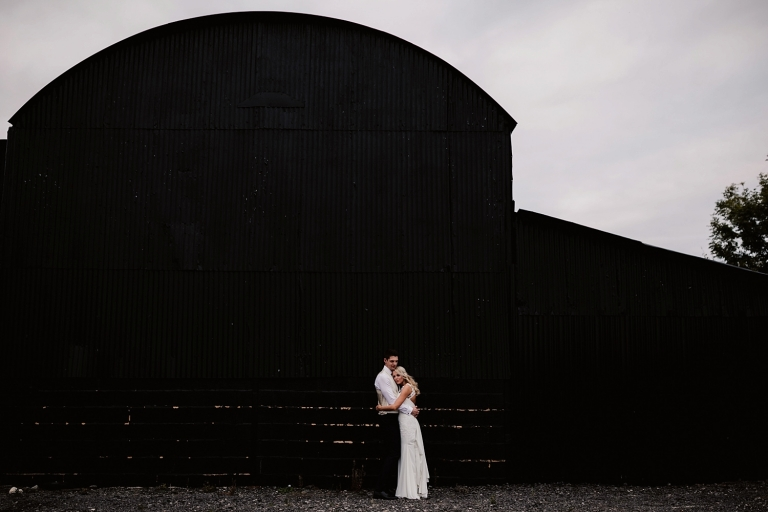 bride and groom outside at barn at caswell house wedding oxfordshire