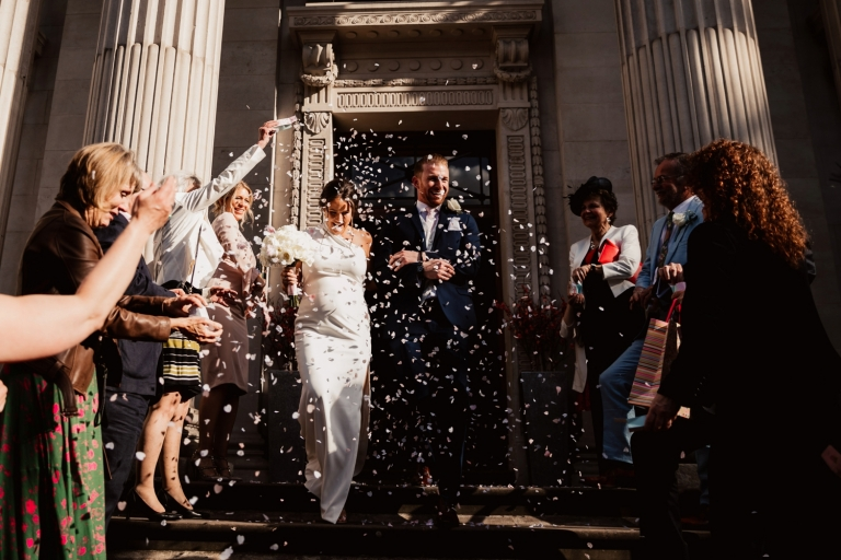 confetti photo in the sun on steps outside old marylebone town hall wedding