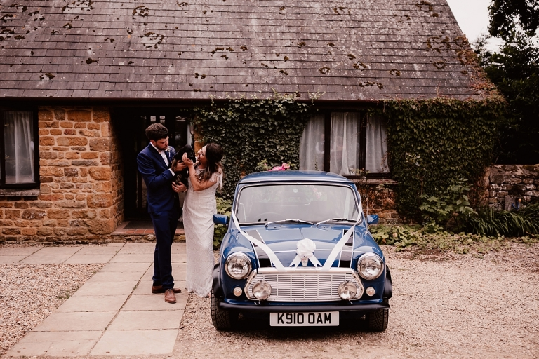 bride and groom with vintage mini and their dog at dovecote barn wedding oxfordshire