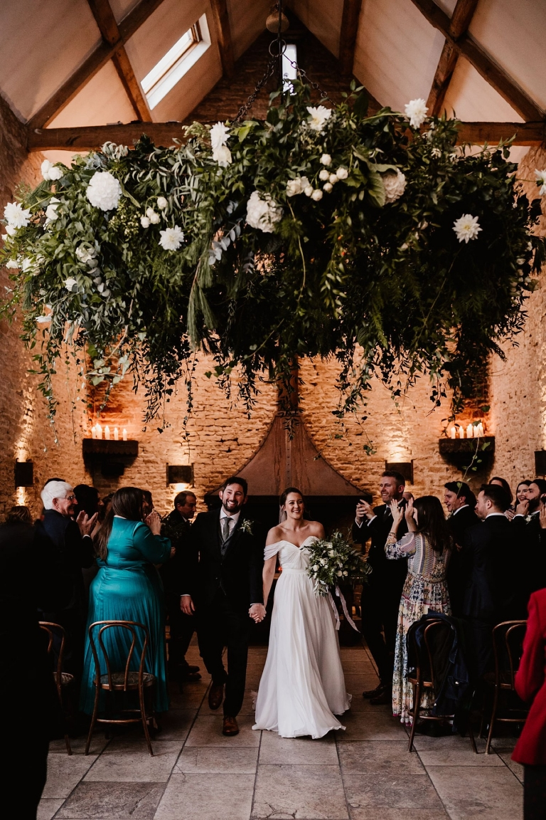 Bride and groom walking out of wedding ceremony at stone barn cotswolds